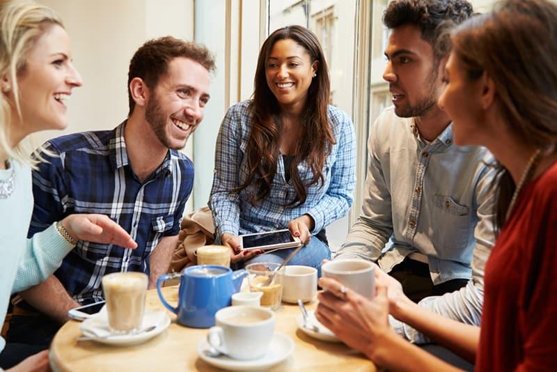 eine Gruppe von Freunden, die im Café lachen