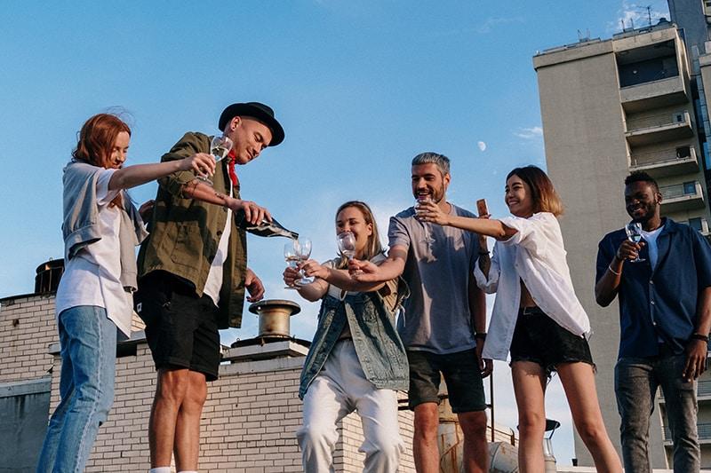 Eine Gruppe von Freunden hält ein Glas in der Hand und wartet darauf, es auf der Party mit Champagner zu füllen