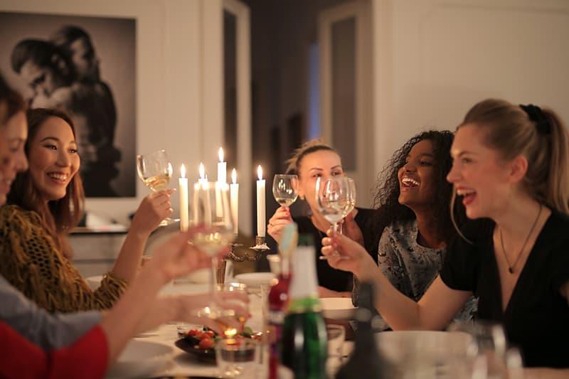 eine Gruppe von Freundinnen, die während eines Abendessens auf einer Geburtstagsfeier einen Toast trinken