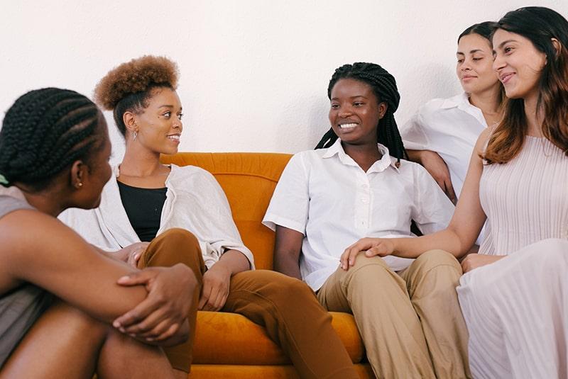 Eine Gruppe von Freundinnen unterhält sich auf dem Sofa
