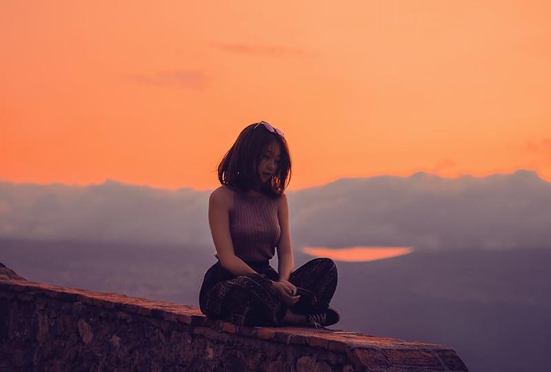 eine einsame Frau, die während des Sonnenuntergangs auf der Betonwand sitzt