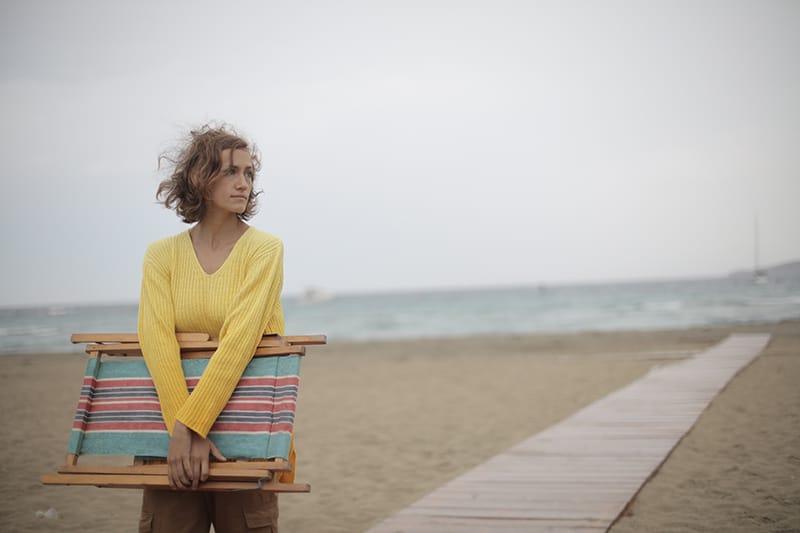 eine einsame Frau, die einen hölzernen Strandkorb trägt und nachdenklich aussieht, während sie auf dem Sand geht