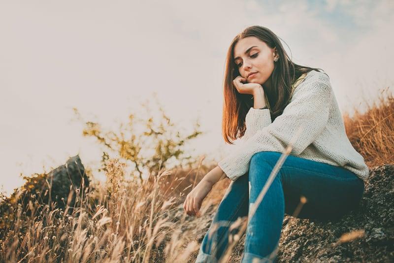 eine einsame Frau, die auf dem Boden sitzt und nach unten schaut