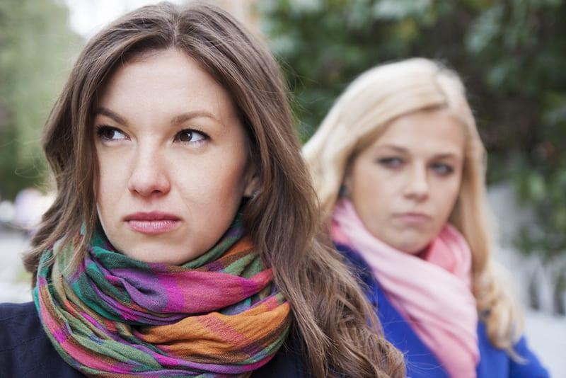 eine enttäuschte Frau, die in der Nähe einer Freundin steht und zur Seite schaut