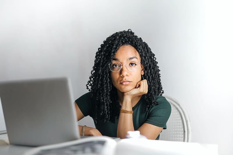 Eine ernsthafte Frau, die den Kopf auf die Handfläche lehnt und vor dem Laptop sitzt