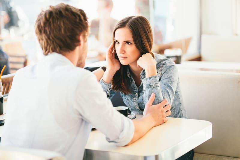 eine ernsthafte Frau, die auf einen Mann schaut, der ihre Hände berührt, während er zusammen im Café sitzt