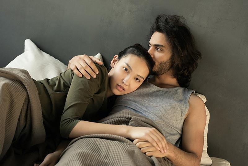 Eine ernsthafte Frau stützte sich auf die Brust des Mannes, während er sie im Bett umarmte
