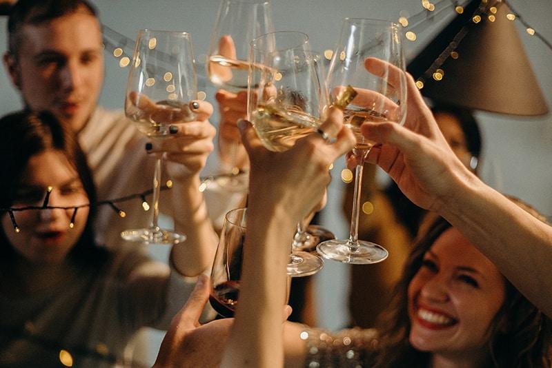 eine fröhliche Gruppe von Freunden, die einen Toast mit einem Glas Wein trinkenv