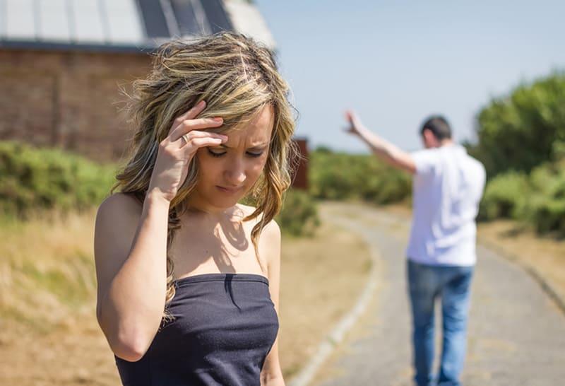 eine frustrierte Frau, die nach unten schaut, während ein Mann von ihr geht