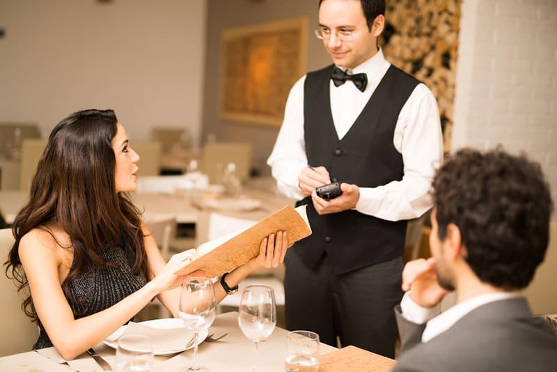 eine höfliche Frau, die bei einem Kellner bestellt, während sie mit einem Mann am Tisch sitzt