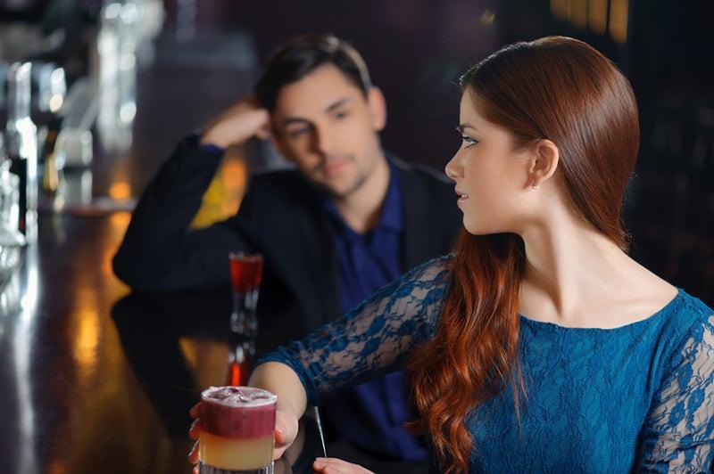 eine junge attraktive Frau, die sich wieder einem jungen Mann zuwendet, der an der Bartheke sitzt