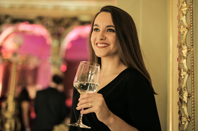 eine lächelnde Dame, die ein Glas Wein hält, während sie allein auf der Party steht