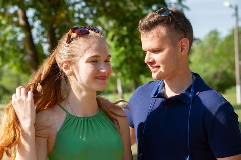 eine lächelnde Frau, die Haare berührt, ein Mann, der sie beim gemeinsamen Gehen im Park ansieht