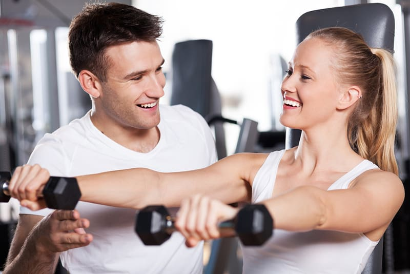 eine lächelnde Frau, die Hanteln hebt, während ein lächelnder Mann sie im Körpergymnastik unterstützt