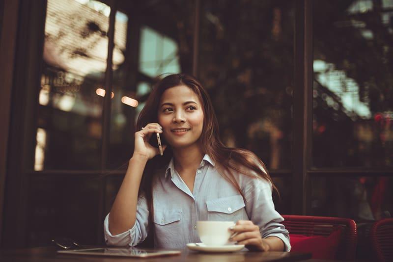 eine lächelnde Frau, die am Telefon spricht, während sie im Café sitzt