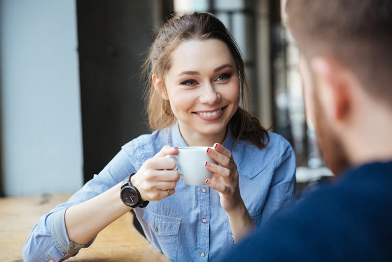 eine lächelnde Frau, die eine Tasse Kaffee hält und zu einem Mann schaut, der mit ihr sitzt