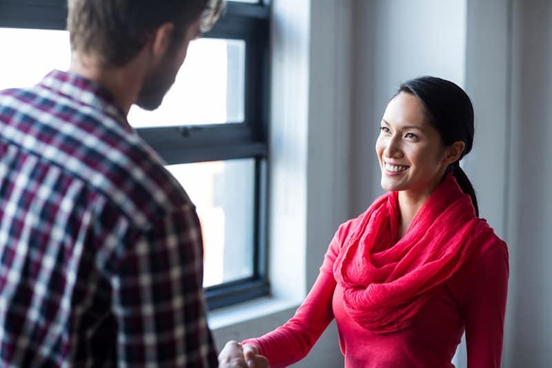 eine lächelnde Frau, die einem Mann die Hand schüttelt, während sie in der Nähe des Fensters steht