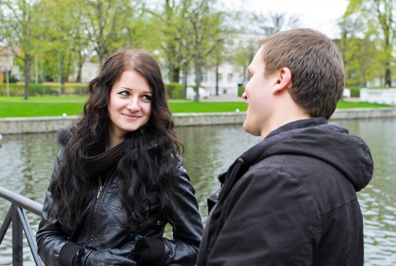 eine lächelnde Frau, die einen Mann betrachtet, während sie zusammen in der Nähe des Teiches im Park steht