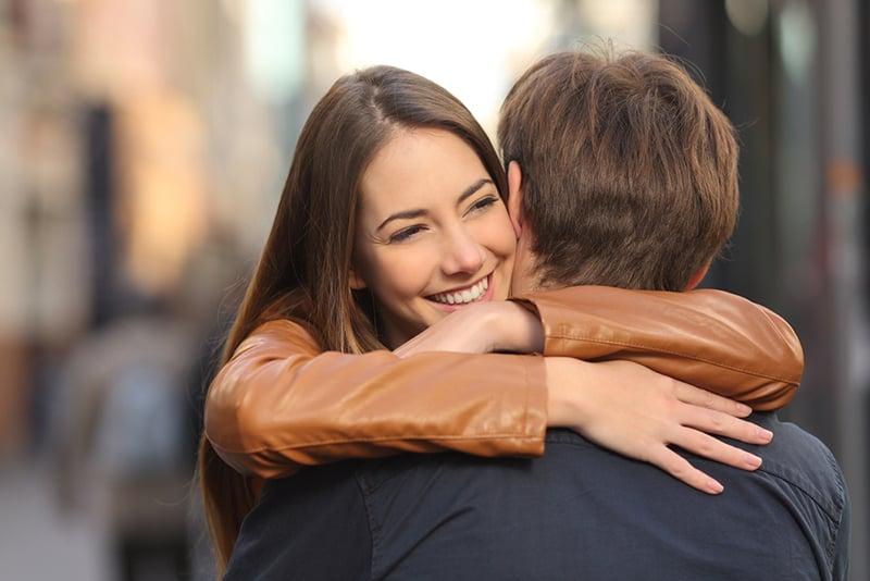 eine lächelnde Frau, die einen Mann umarmt, während sie auf der Straße steht