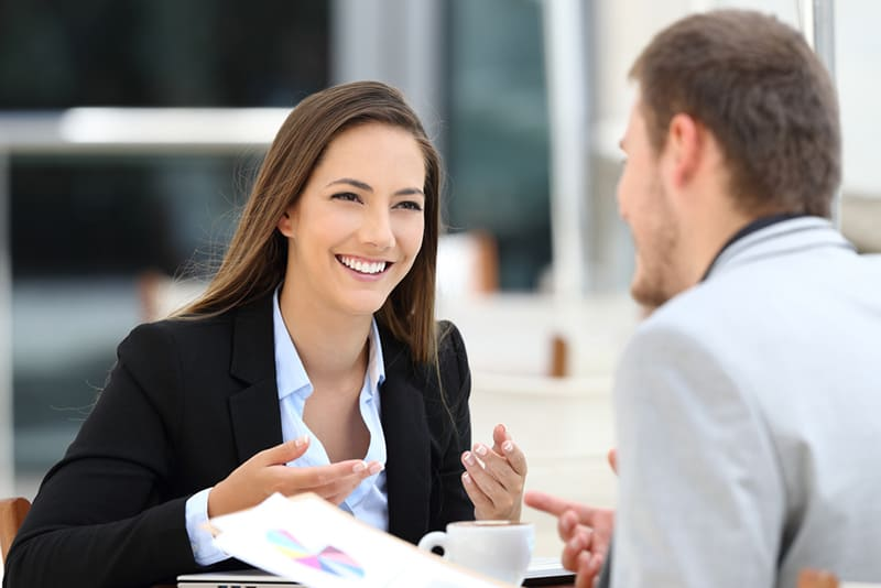 eine lächelnde Frau, die mit einem männlichen Kollegen spricht, während sie zusammenarbeitet und einen Kaffee trinkt
