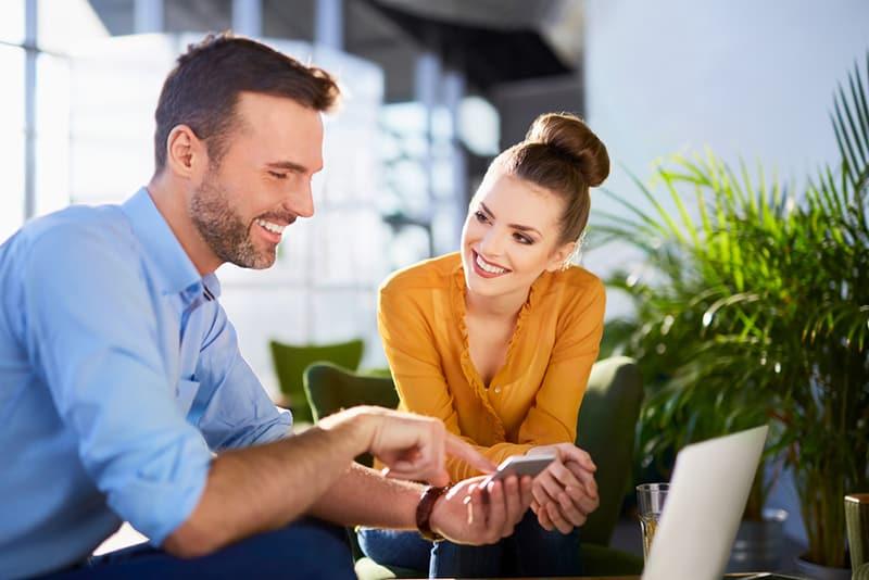 Eine lächelnde Frau, die auf einen Mann schaut, der errötet aussieht, während sie lächelt und ihr etwas auf dem Smartphone zeigt