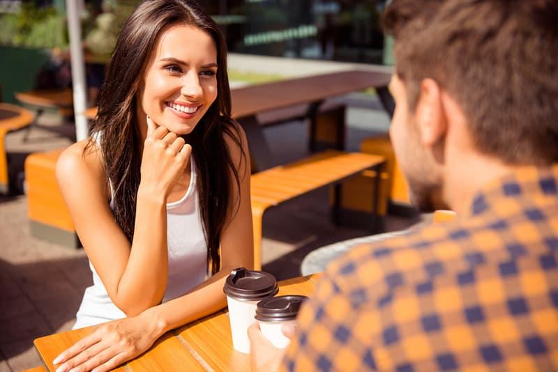 eine lächelnde Frau, die zu ihrem männlichen Freund schaut, während sie zusammen im Café sitzt