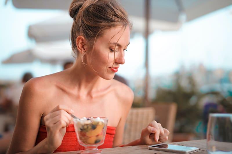 eine lächelnde Frau, die ein Smartphone benutzt, während sie im Café sitzt und Obstsalat isst