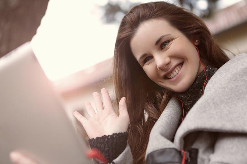 eine lächelnde Frau, die während eines Videoanrufs winkt