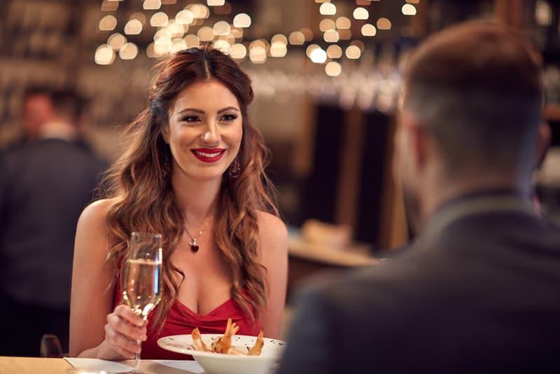 eine lächelnde selbstbewusste Frau, die mit einem Mann im Restaurant sitzt und ein Glas Champagner hält