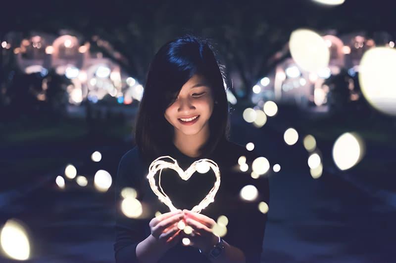 eine lächelnde Frau, die ein herzförmiges Licht in der Nacht hält
