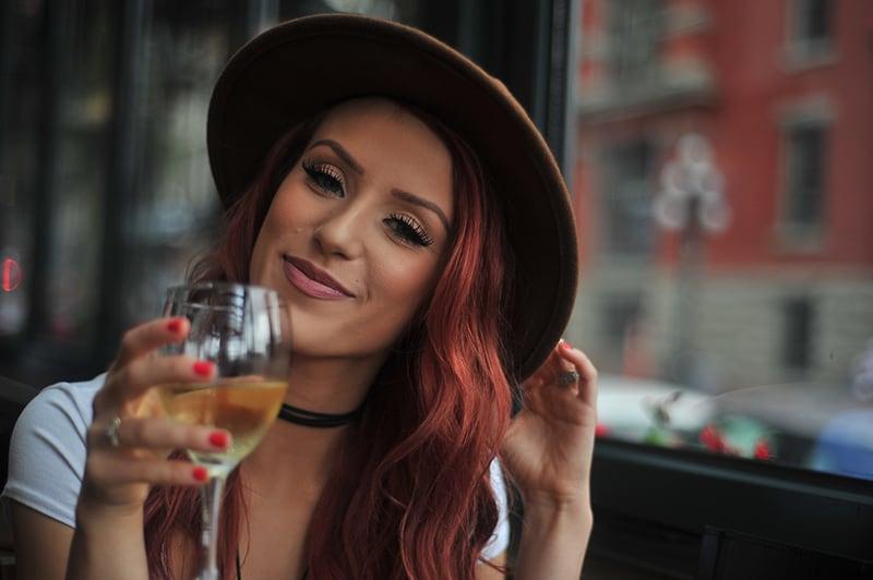 eine lächelnde Frau, die einen Hut trägt, der ein Glas Wein hält