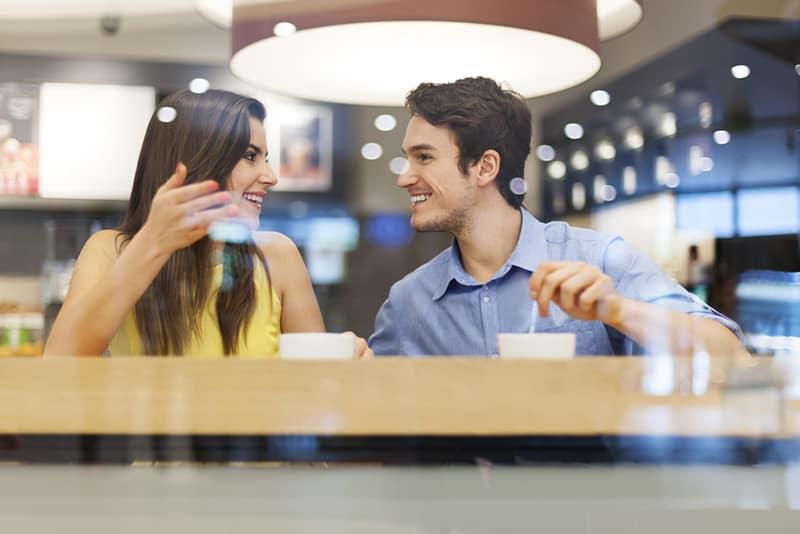 eine lächelnde Frau, die mit einem lächelnden Mann im Café am Datum spricht