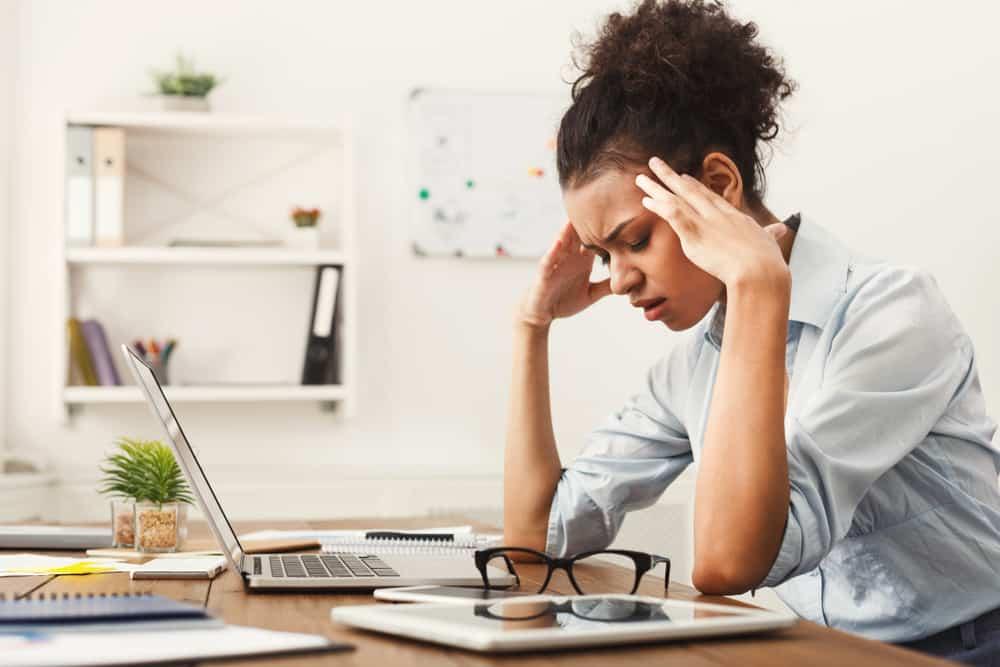 eine müde Geschäftsfrau, die an einem Tisch sitzt und den Kopf hält