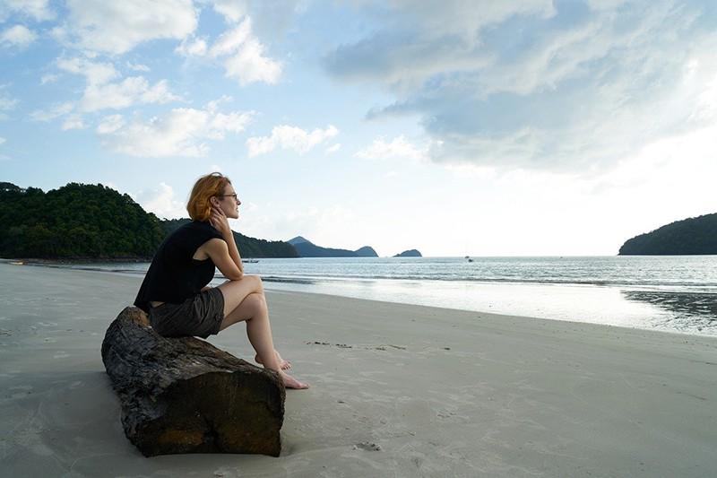 eine nachdenkliche Frau, die alleine am Strand sitzt und auf das Meer schaut