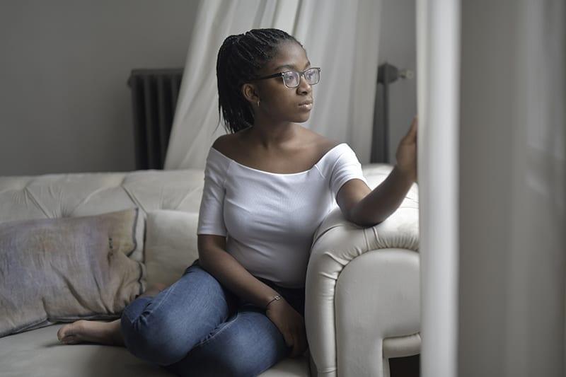 eine nachdenkliche Frau, die auf dem Sofa sitzt und durch das Fenster schaut