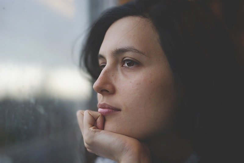 eine nachdenkliche Frau, die durch das Fenster schaut und das Kinn zur Hand lehnt