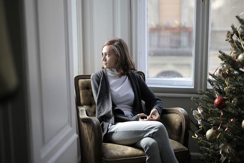 eine nachdenkliche Frau, die im Sessel sitzt und durch das Fenster schaut