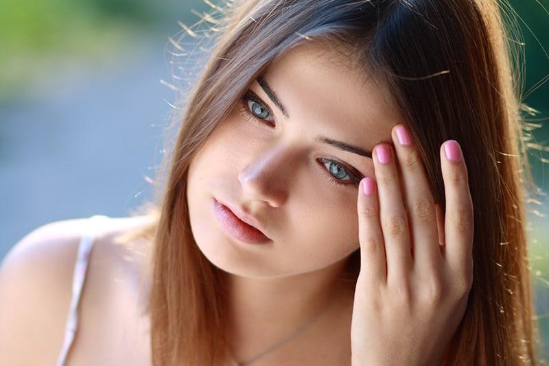 eine nachdenkliche Frau, die nach unten schaut, während sie Haare berührt