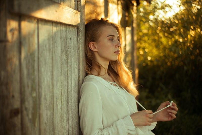 eine nachdenkliche Frau, die sich an die Holzwand stützt, während sie draußen steht
