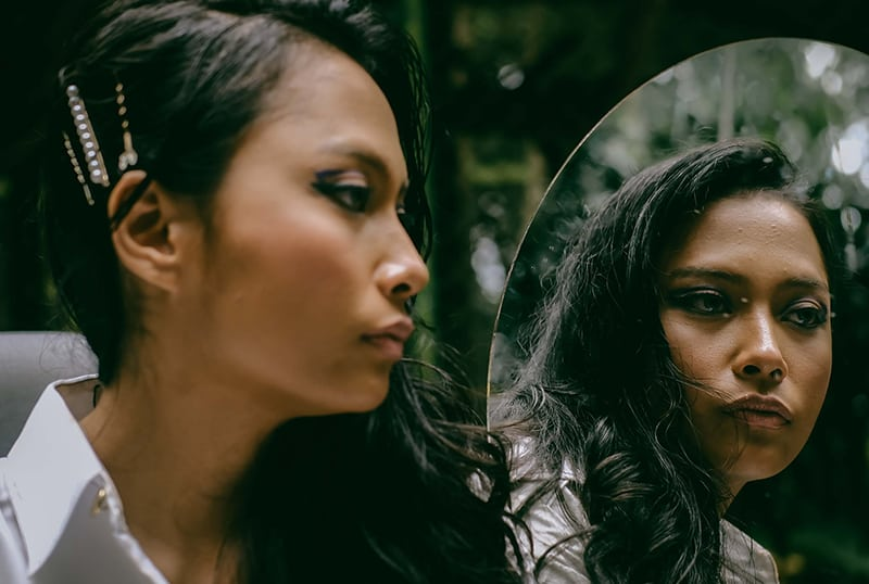 eine nachdenkliche Frau, die vor dem Spiegel steht und zur Seite schaut