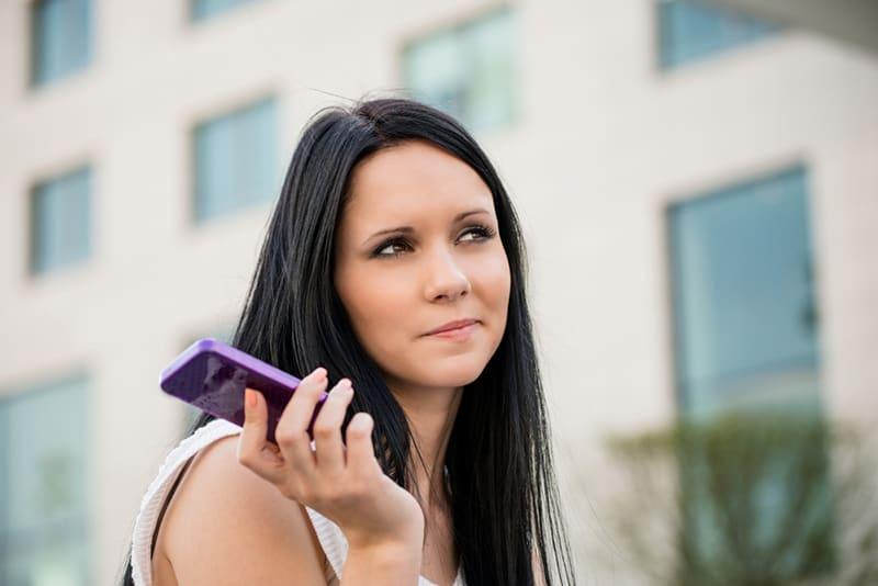 eine nachdenkliche Frau, die beiseite schaut, während sie ein Smartphone in der rechten Hand hält