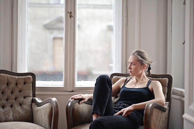eine nachdenkliche Frau, die auf dem Sessel neben dem Fenster sitzt