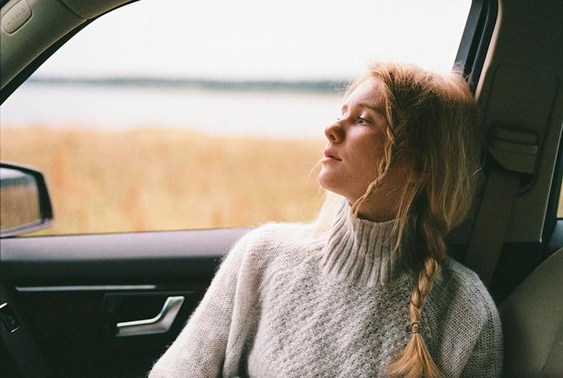 eine nachdenkliche Frau, die im Auto sitzt und durch das Fenster schaut
