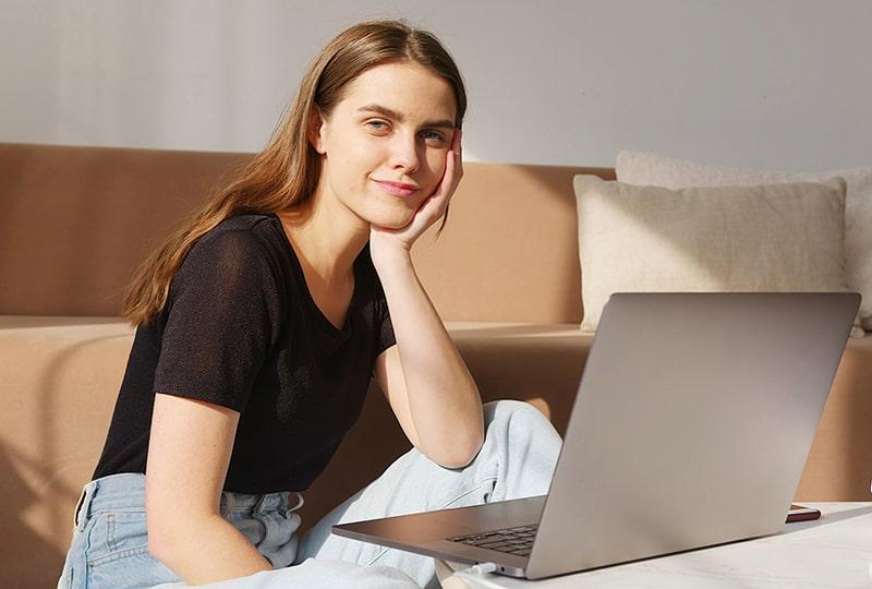 eine positive Frau sitzt auf dem Boden im Wohnzimmer