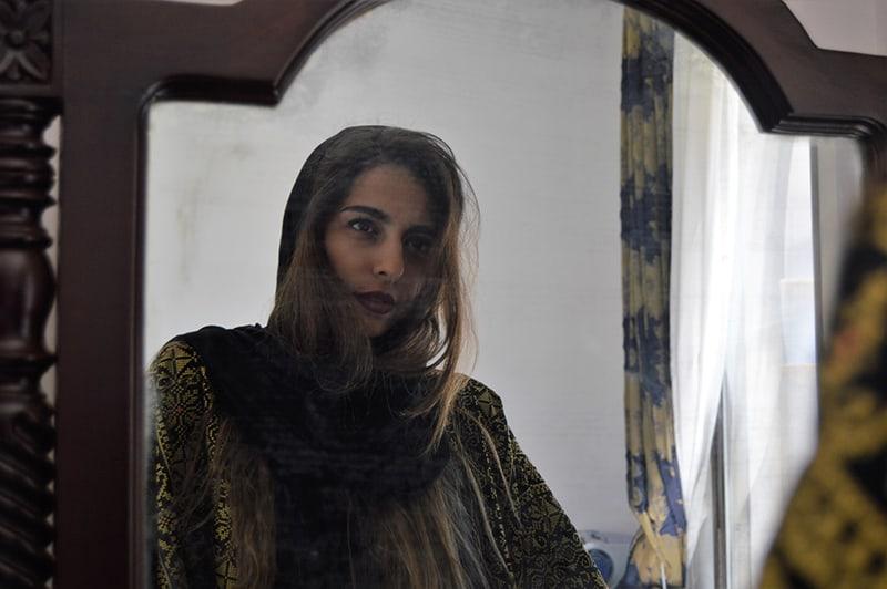 eine selbstbewusste Frau, die sich im Raum im Spiegel betrachtet