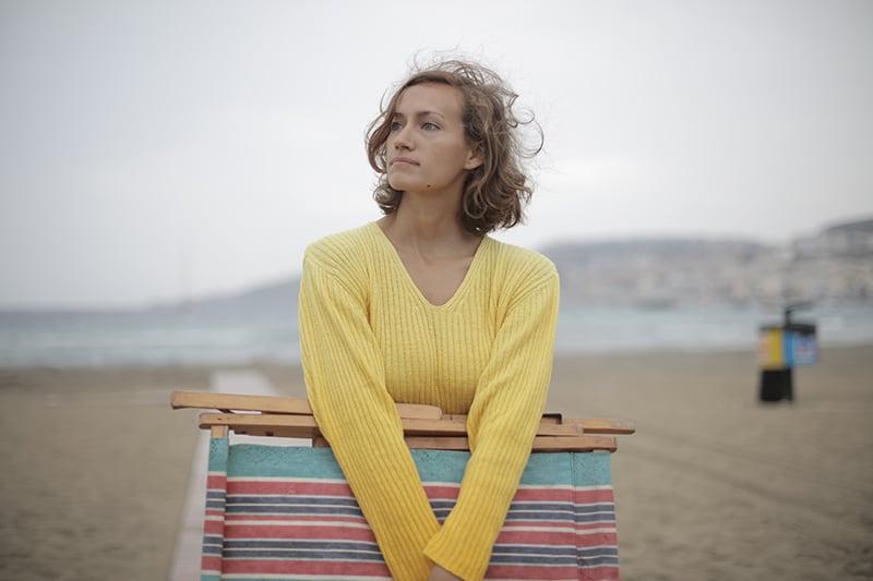 eine traurige Frau, die einen Liegestuhl hält, während sie allein am Strand steht
