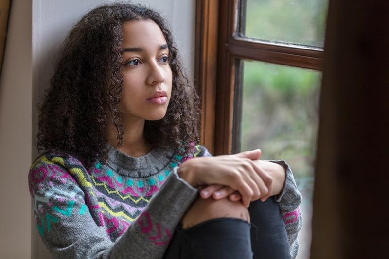 eine traurige Frau, die auf der Fensterbank sitzt und durch sie schaut