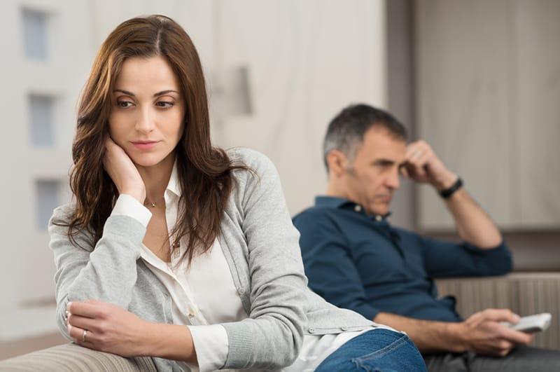 eine traurige Frau, die in der Nähe des Mannes sitzt, während er fernsieht