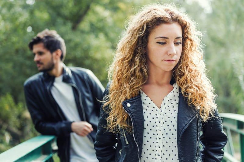 Eine traurige Frau, die nach unten schaut und vor einem Mann steht, der sich auf den Handlauf stützt