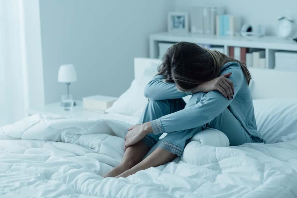 eine traurige Frau im Pyjama, die auf dem Bett sitzt